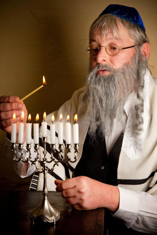 A rabbi lighting the Menorah.